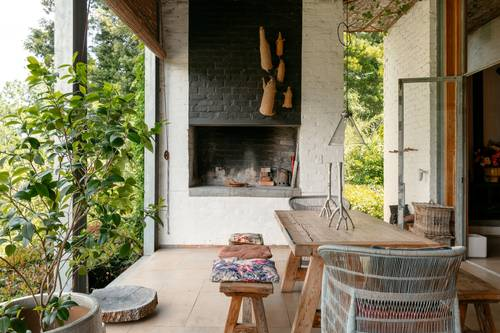 The rustic covered patio with outdoor fireplace