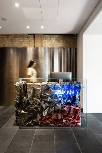 BURSA's reception desk is composed of scrunched-up metal sheets set behind a glass panel.